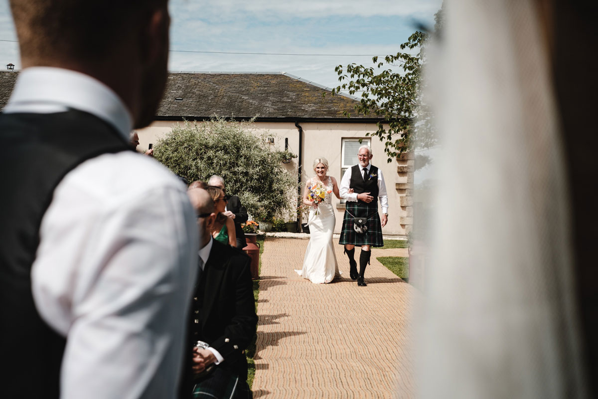bride-walking-up-the-aisle-outside-ceremony
