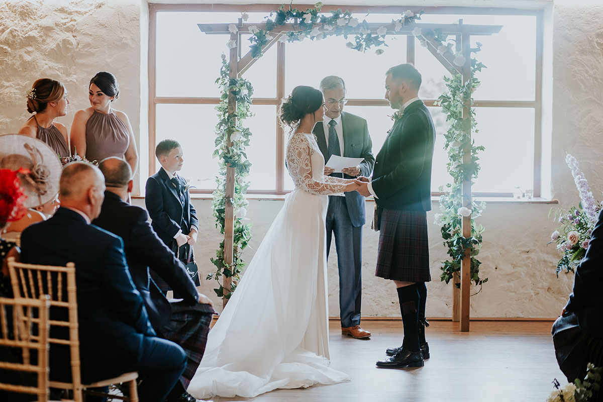 wedding-ceremony-in-barn-with-floral-arch