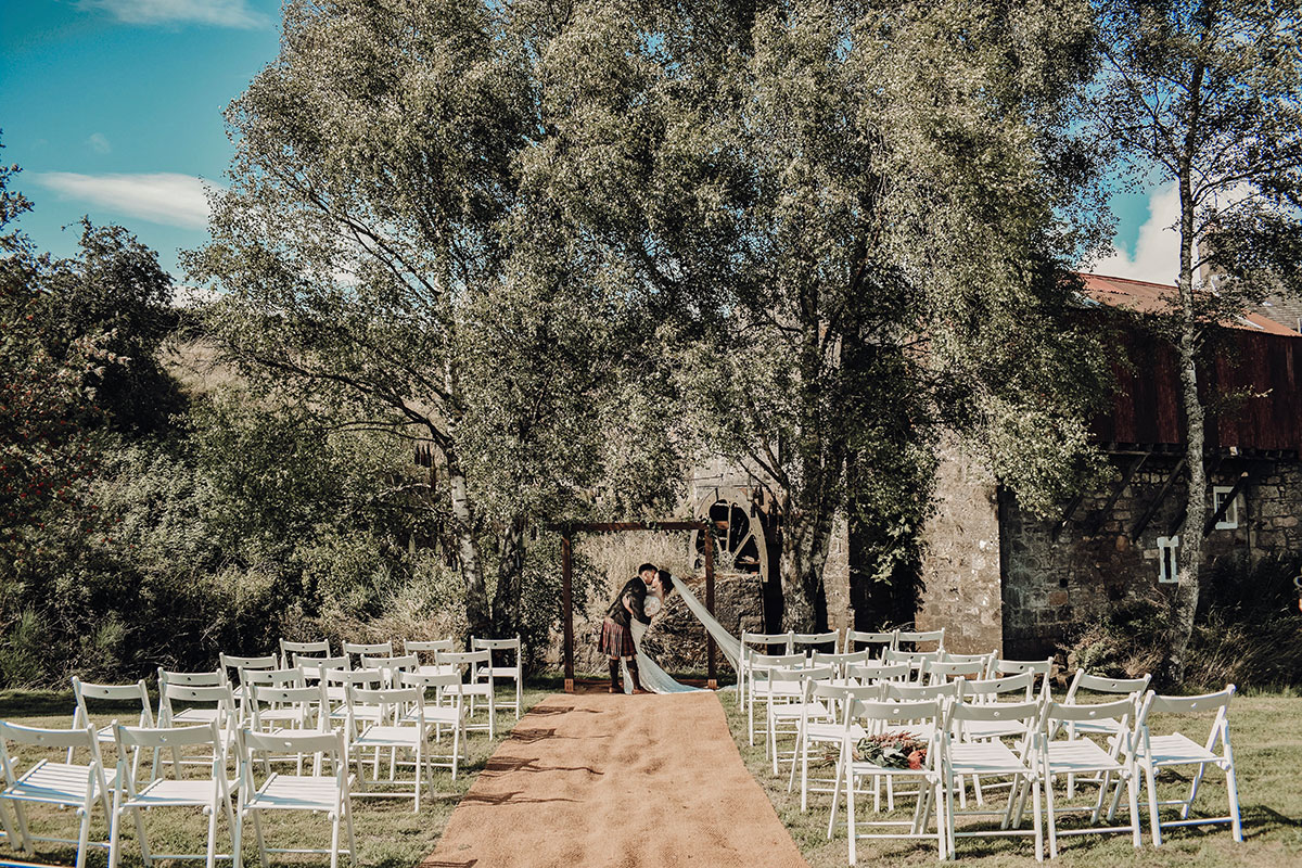 outside-ceremony-with-white-picnic-chairs-set-up
