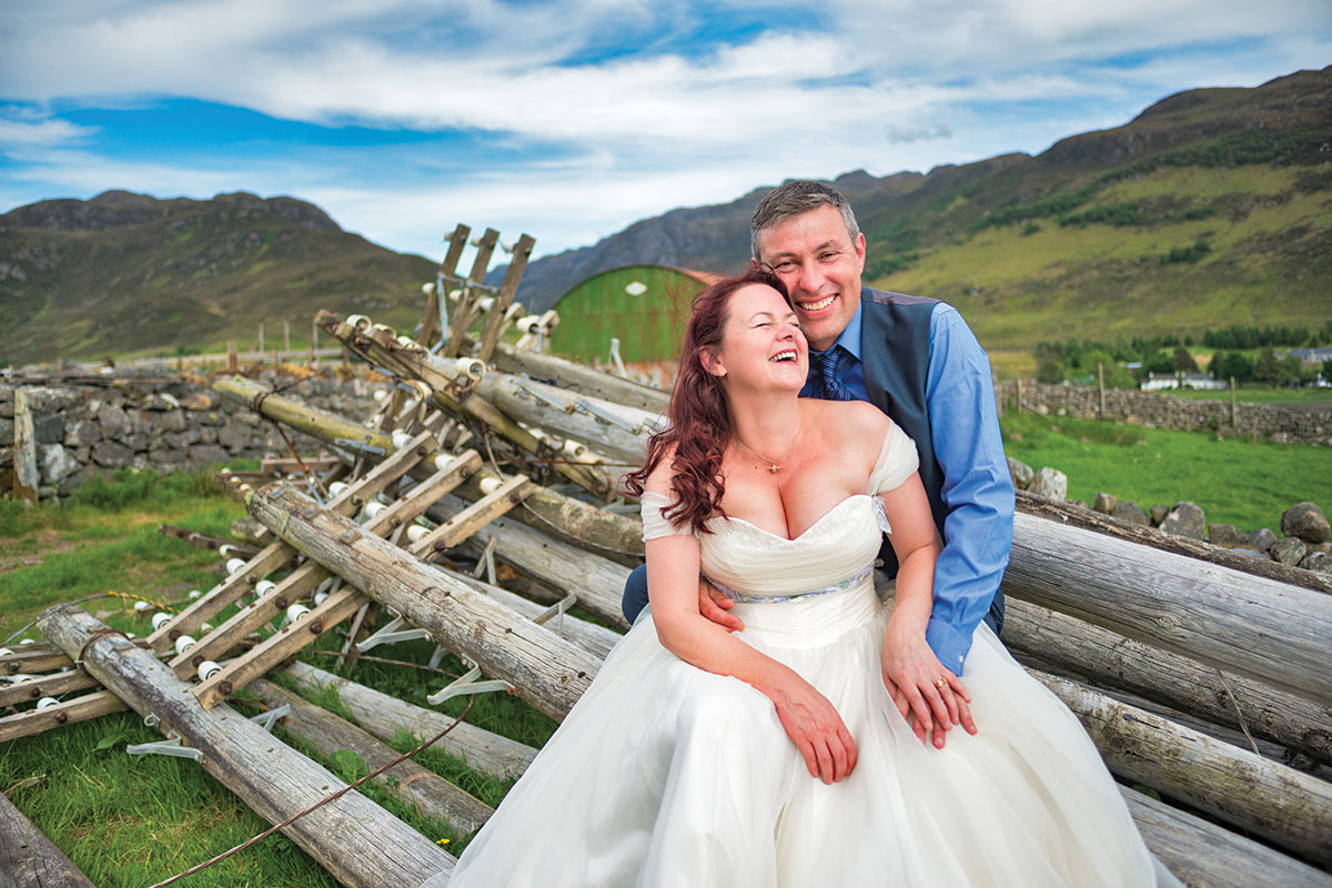 bride-and-groom-sitting-in-a-field
