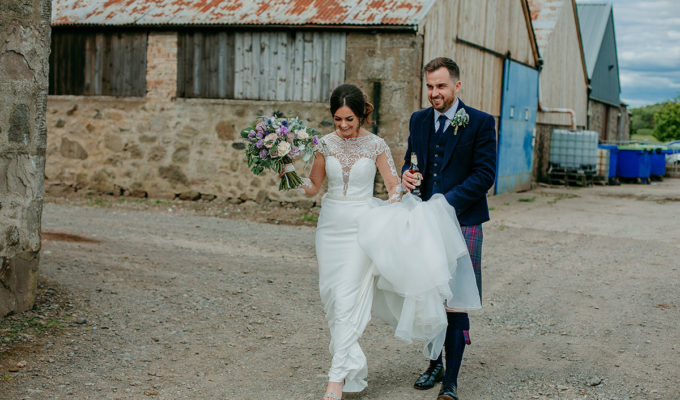 bride-and-groom-walking-through-farm-buildings