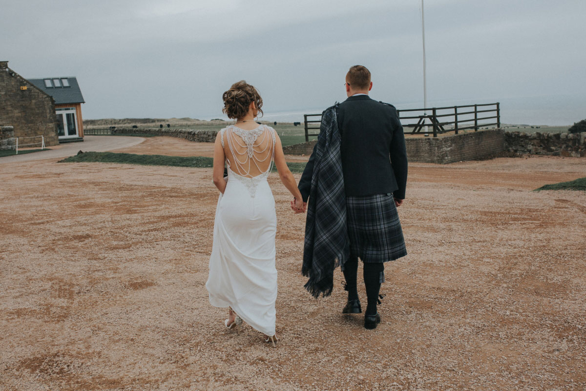 bride-and-groom-walking-to-beach-outside-kinkell-byre