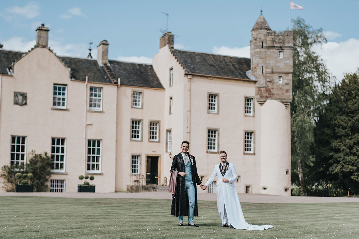 grooms-holding-hands-in-grounds