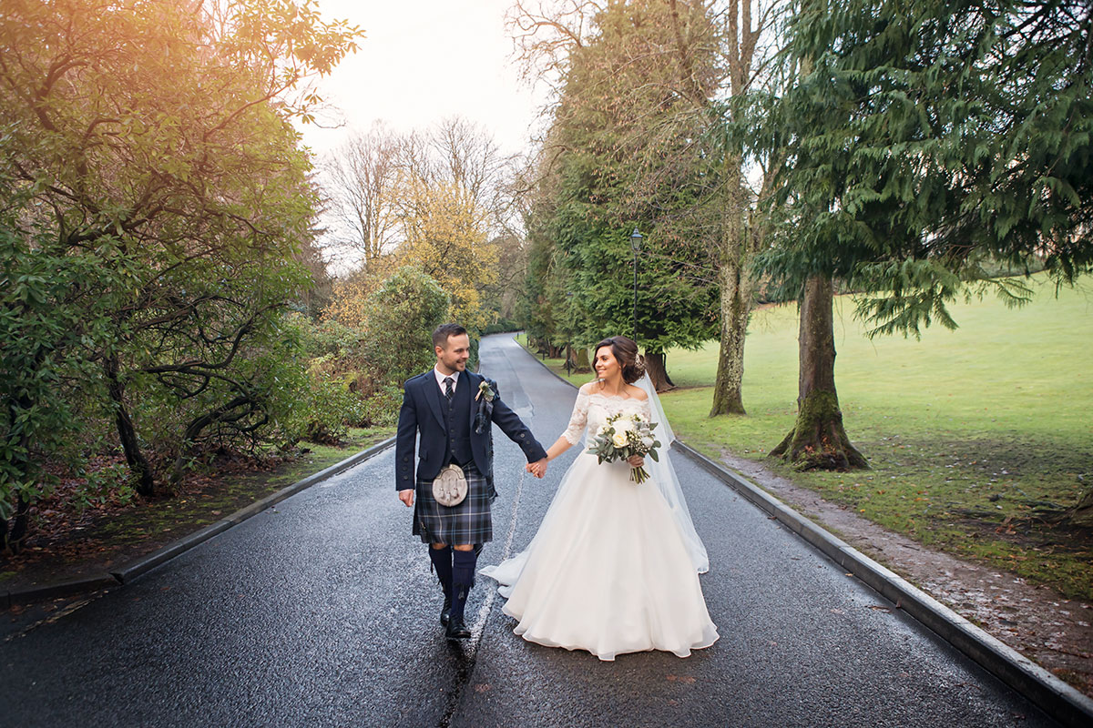 bride-and-groom-walking-down-road-in-perthshire-holding-hands