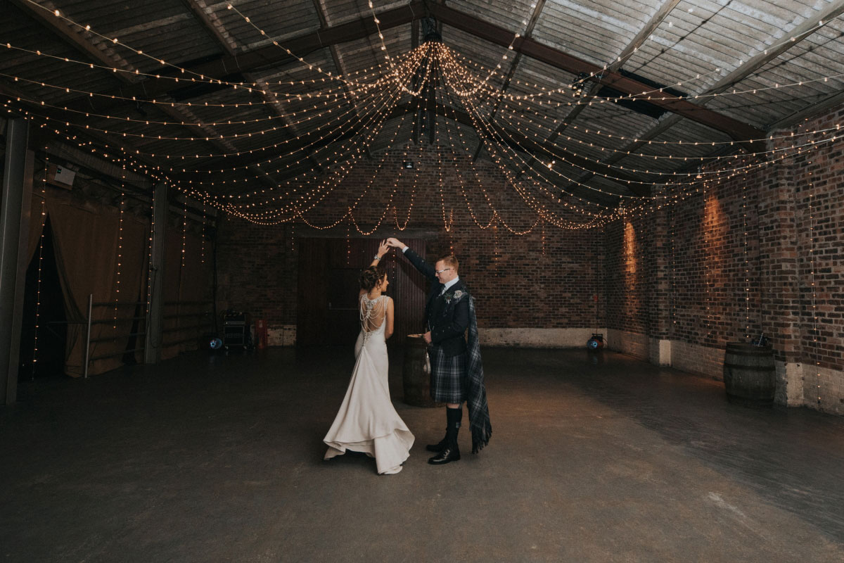 bride-and-groom-dancing-in-empty-room-with-fairy-lights