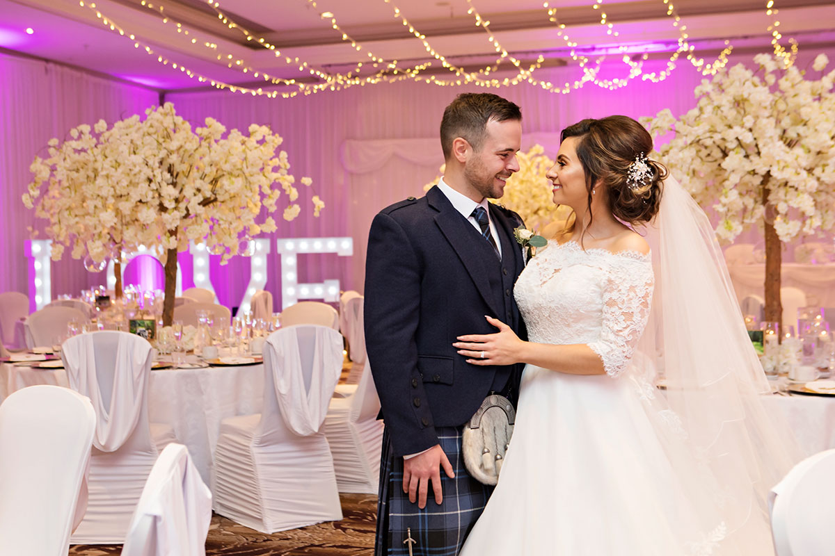 bride-and-groom-in-reception-room-with-purple-uplighting