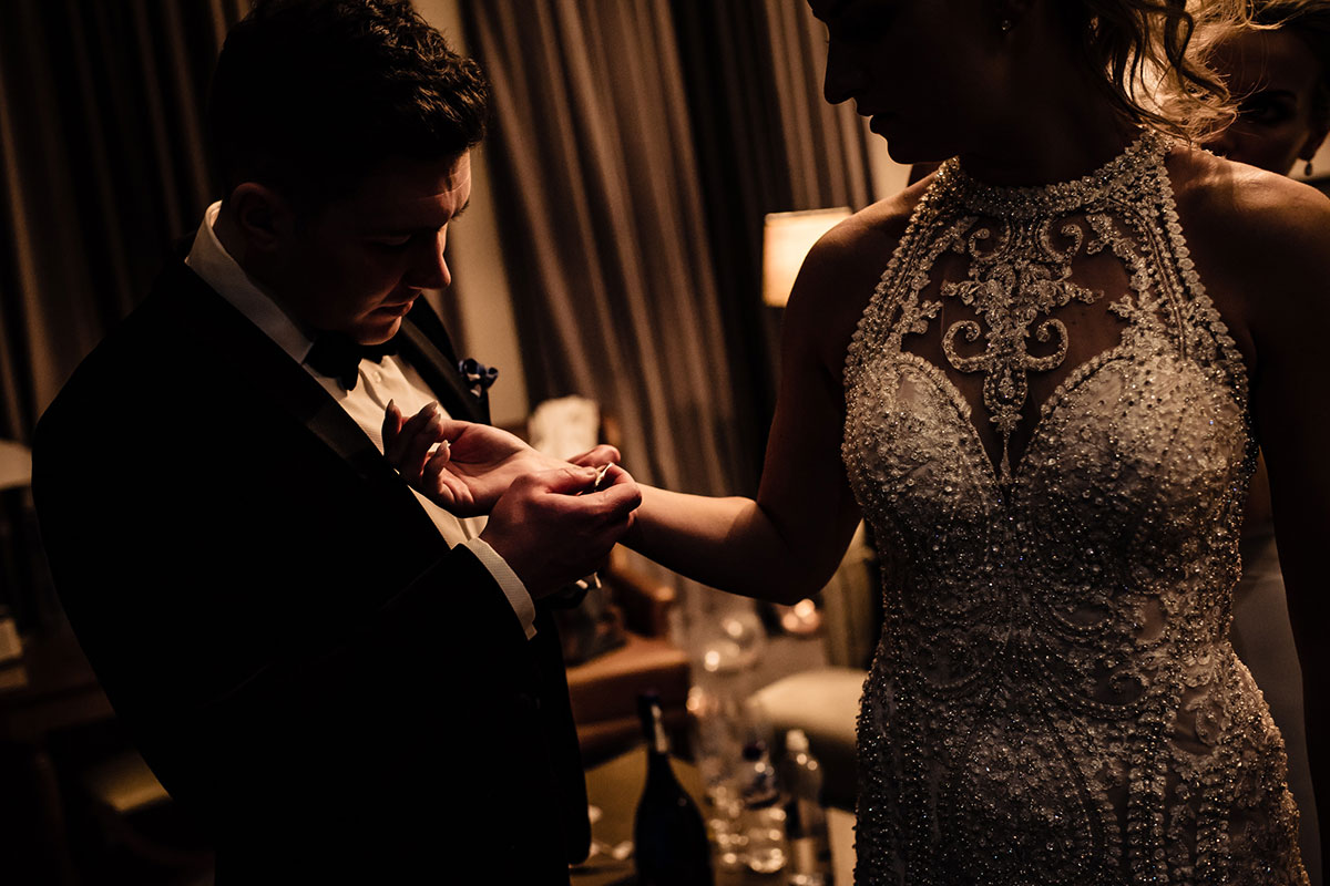groom-putting-on-brides-bracelet-when-she-changed-into-new-dress
