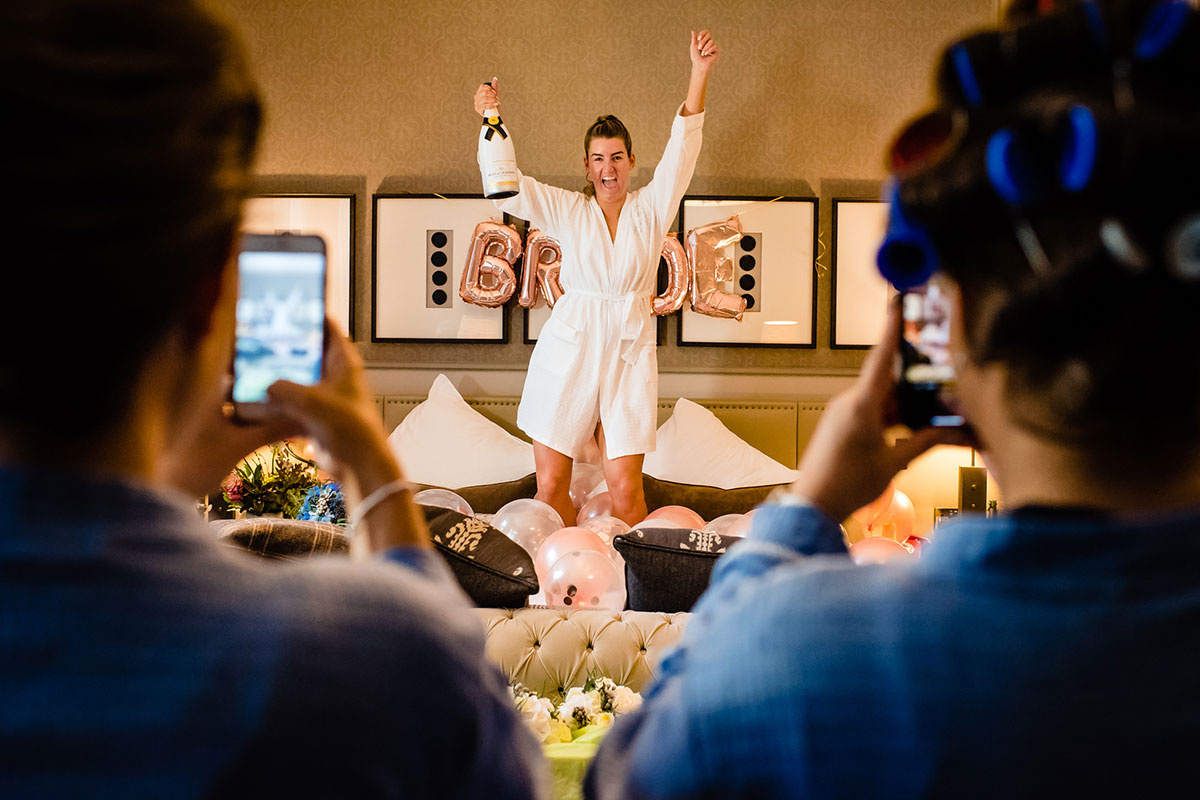 bride-dancing-on-the-bed-drinking-champagne