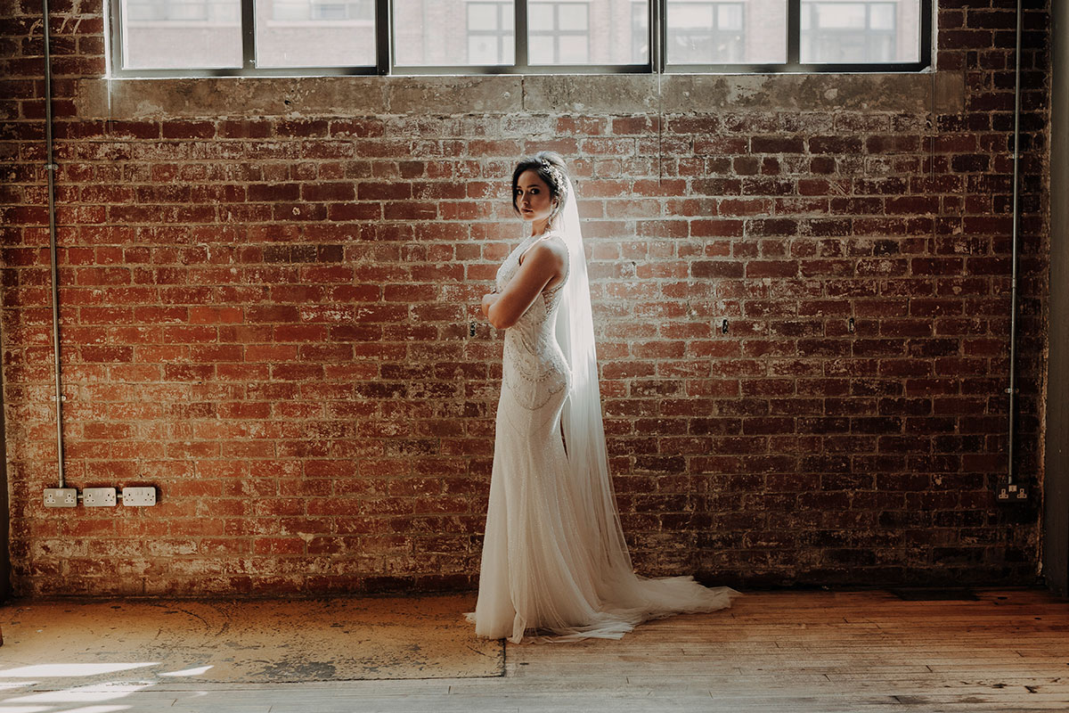 bride-standing-against-brick-wall-in-west-brewery