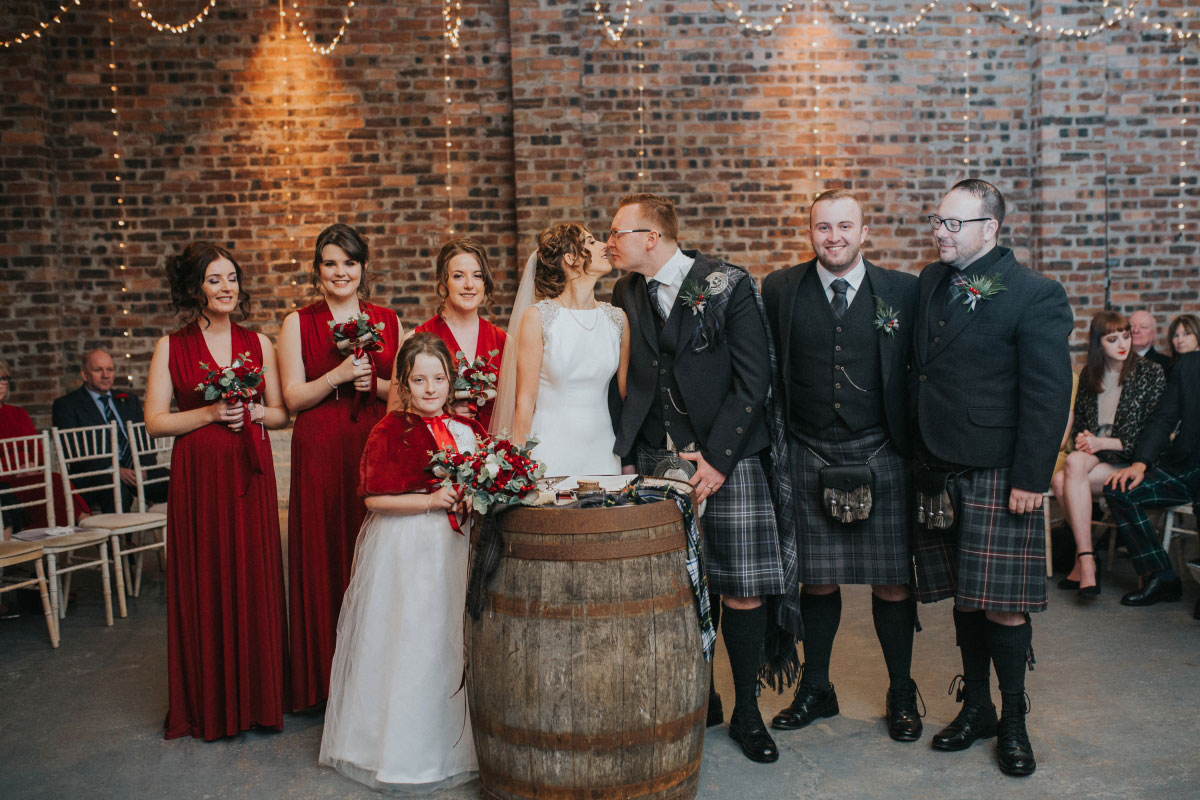 the-bridal-party-in-red-dresses-and-grey-kilts