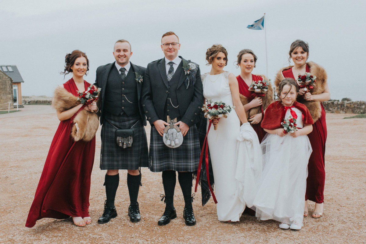 groom-best-man-in-kilts-and-bride-with-bridesmaids-in-red-dresses