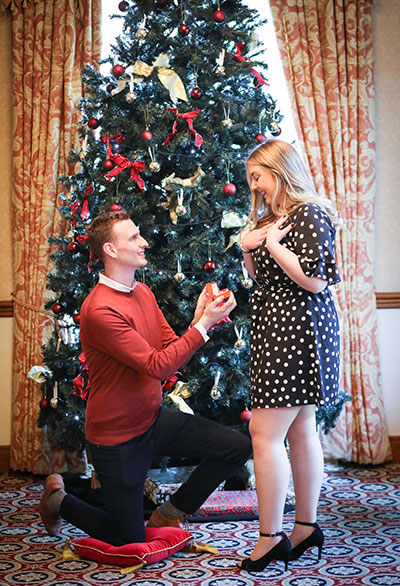 man-proposing-to-woman-in-front-of-christmas-tree
