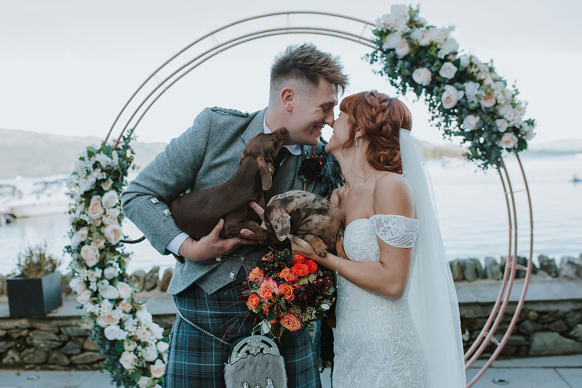 bride-and-groom-under-floral-ring-arch-with-two-sausage-dogs