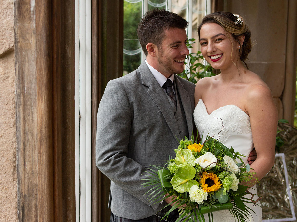 bride-and-groom-with-tropical-floral-arrangement