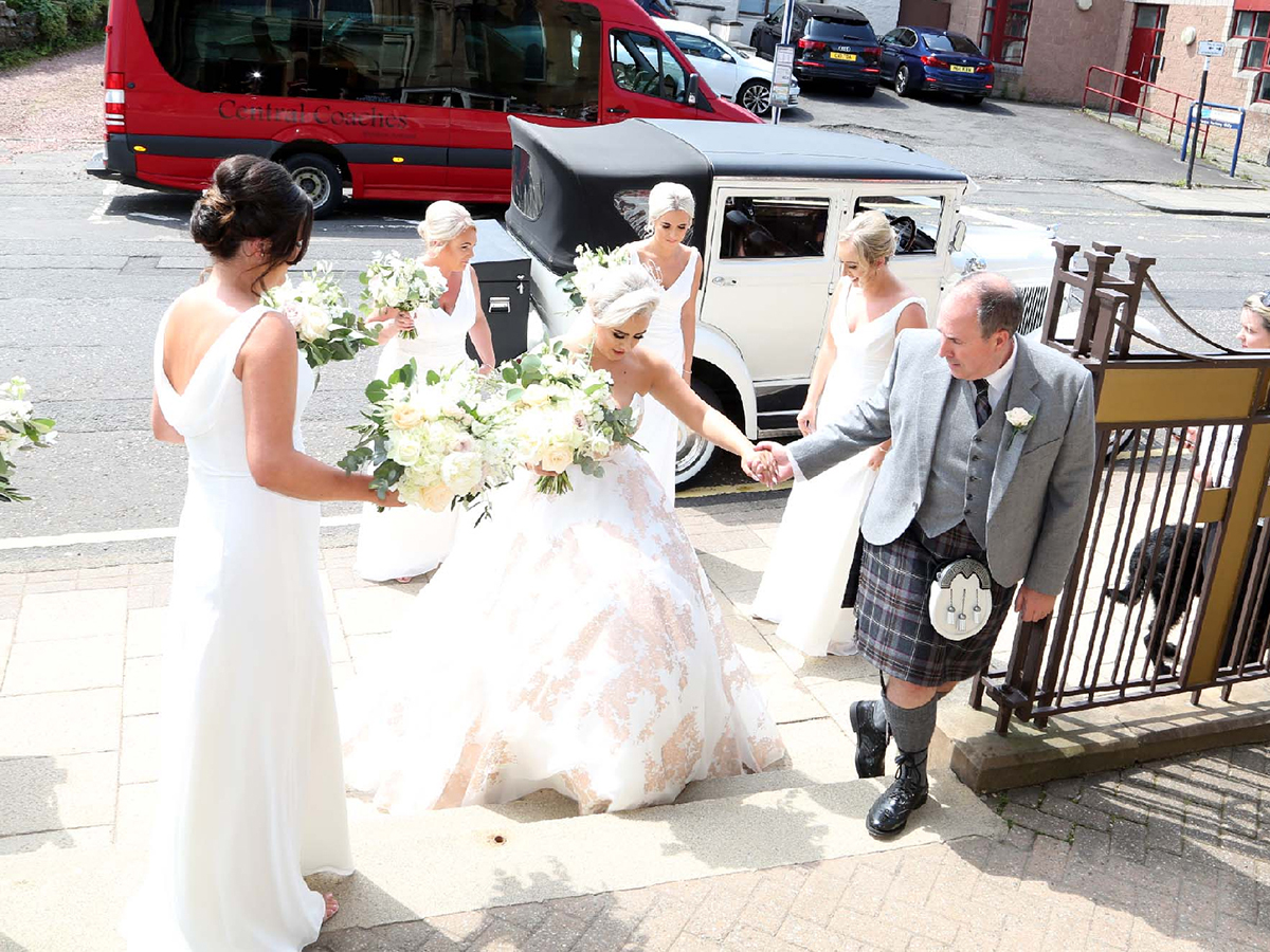 brides-dad-helping-her-up-chapel-steps