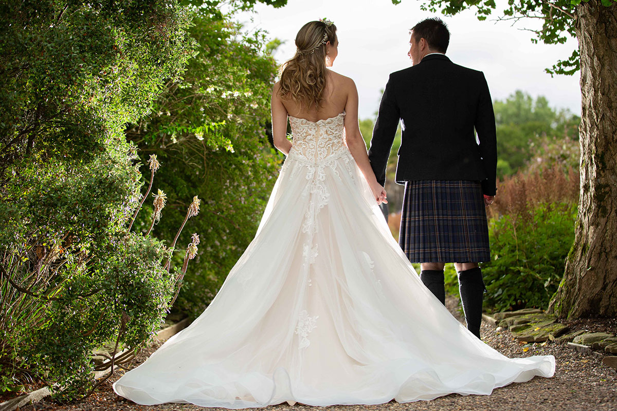 bride-and-groom-holding-hands-in-the-woodlands-near-culzean-castle