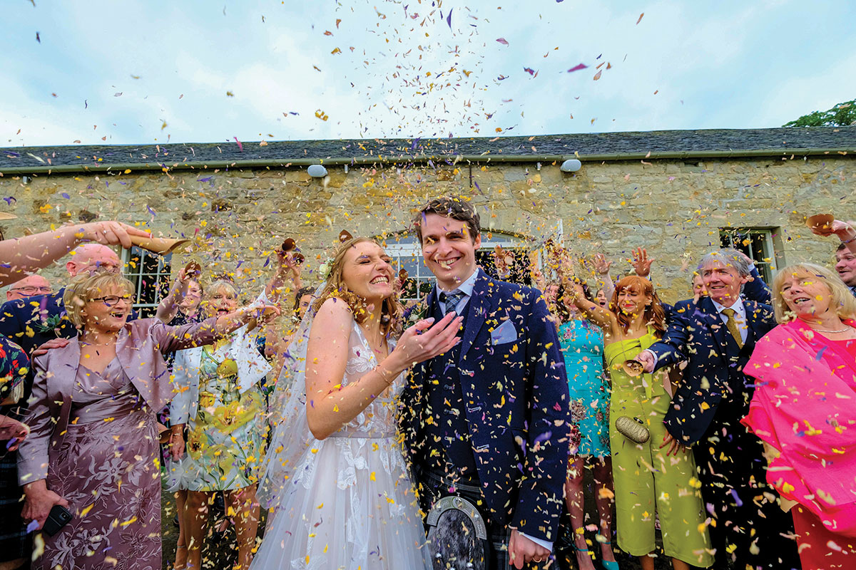 wedding-guests-throwing-confetti-on-happy-couple