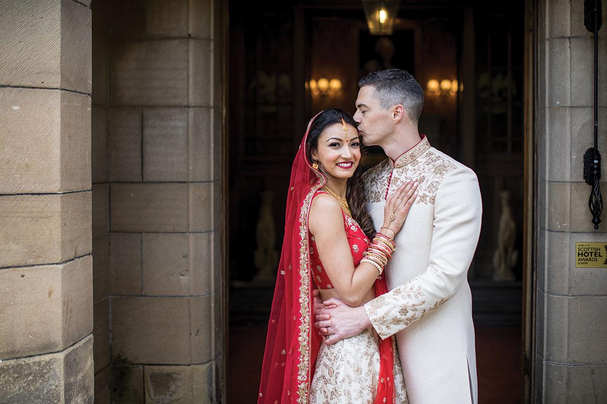bride-and-groom-in-traditional-dress-in-castle-doorway
