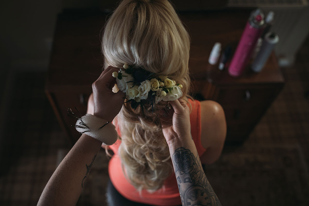 hair-stylist-curling-models-hair-and-attaching-floral-clip