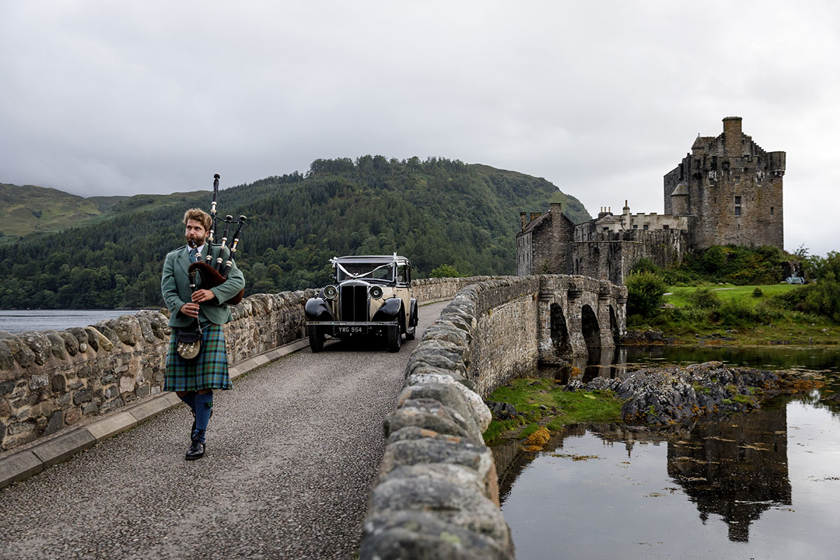 piper-in-front-of-classic-car-outside-eilean-donan-castle