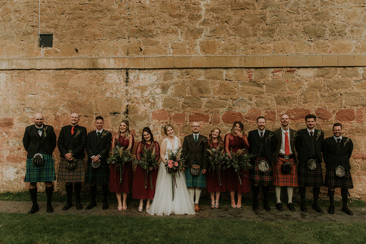 bridal-party-in-red-dresses-and-kilt-outfits