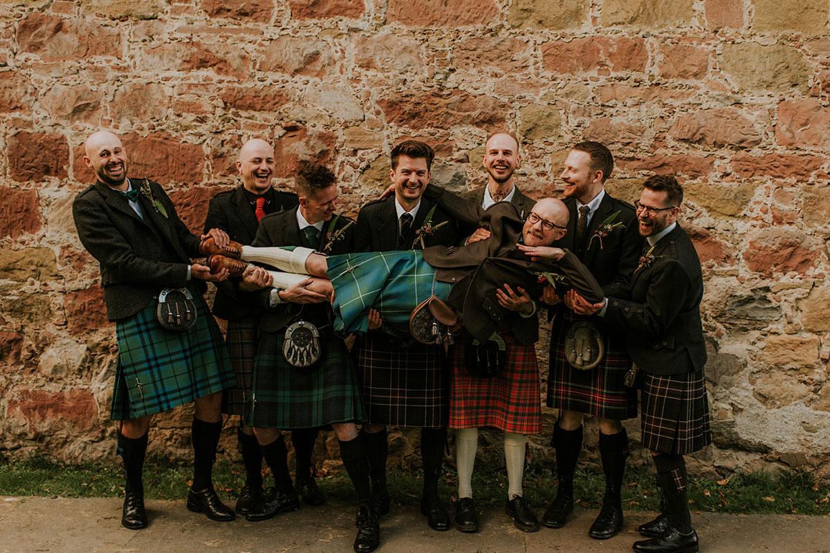 men-in-kilts-holding-up-the-groom