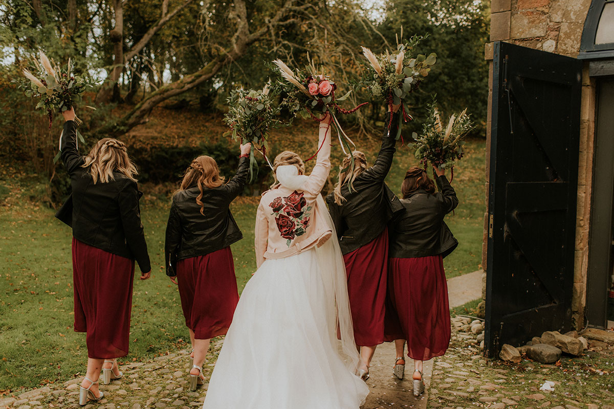 bride-wearing-painted-leather-jacket-and-bridesmaids-in-red-dresses