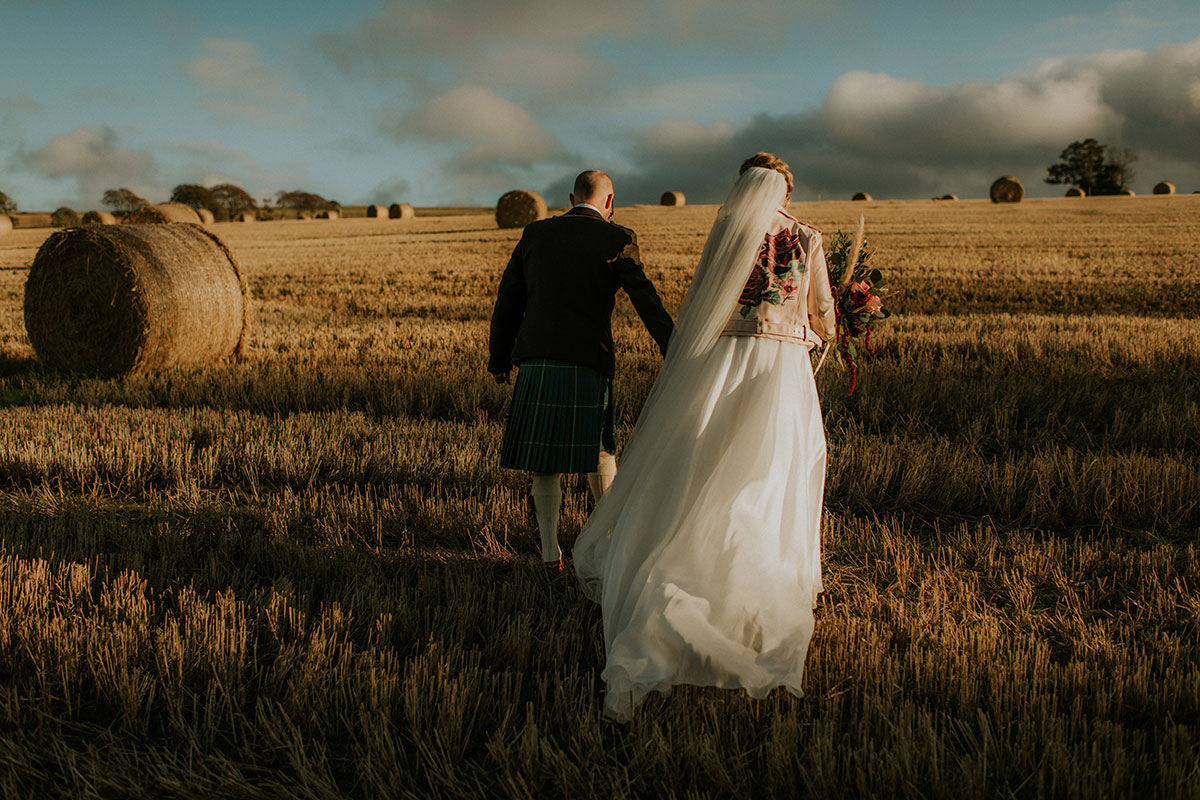 bride-and-groom-walking-in-field-with-bales-of-hay