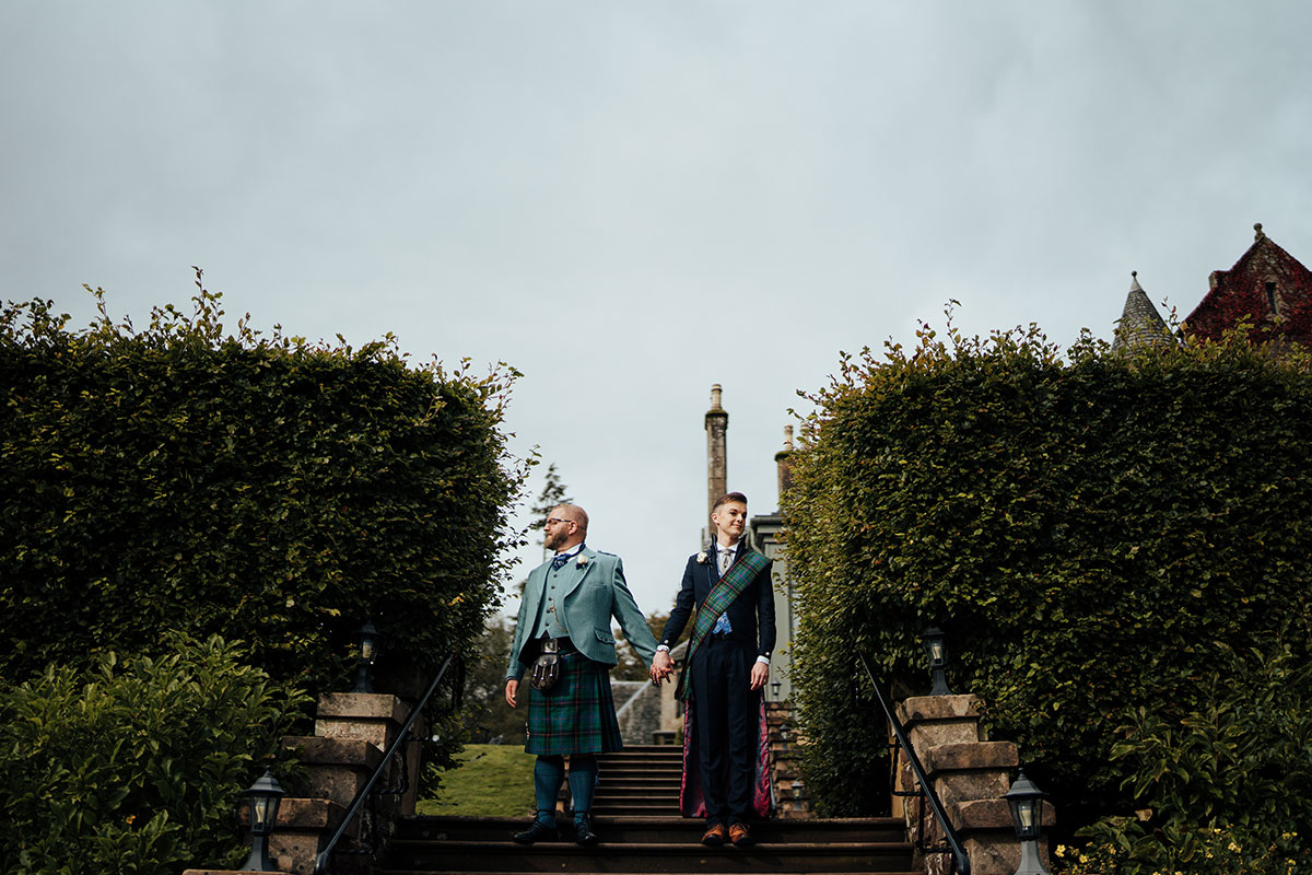 groom-in-kilt-outfit-holding-hands-with-groom-in-atelier-rahman-suit