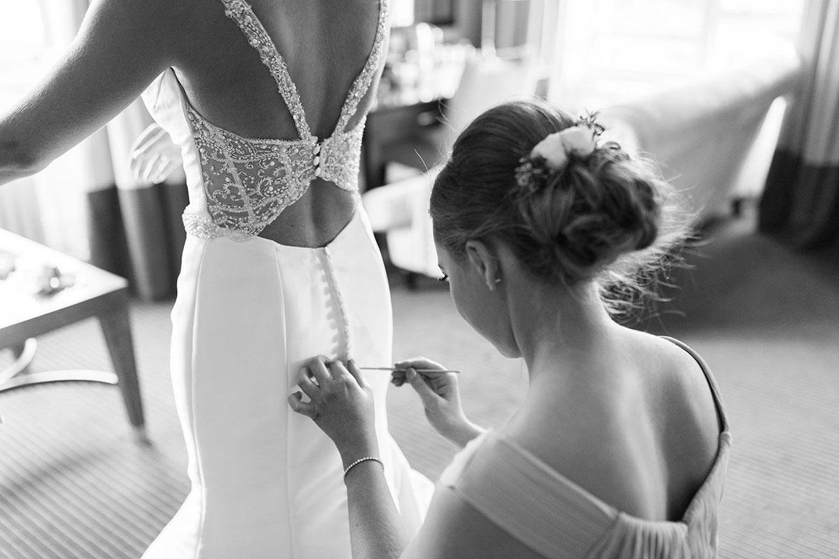 bridesmaid-lacing-up-brides-dress