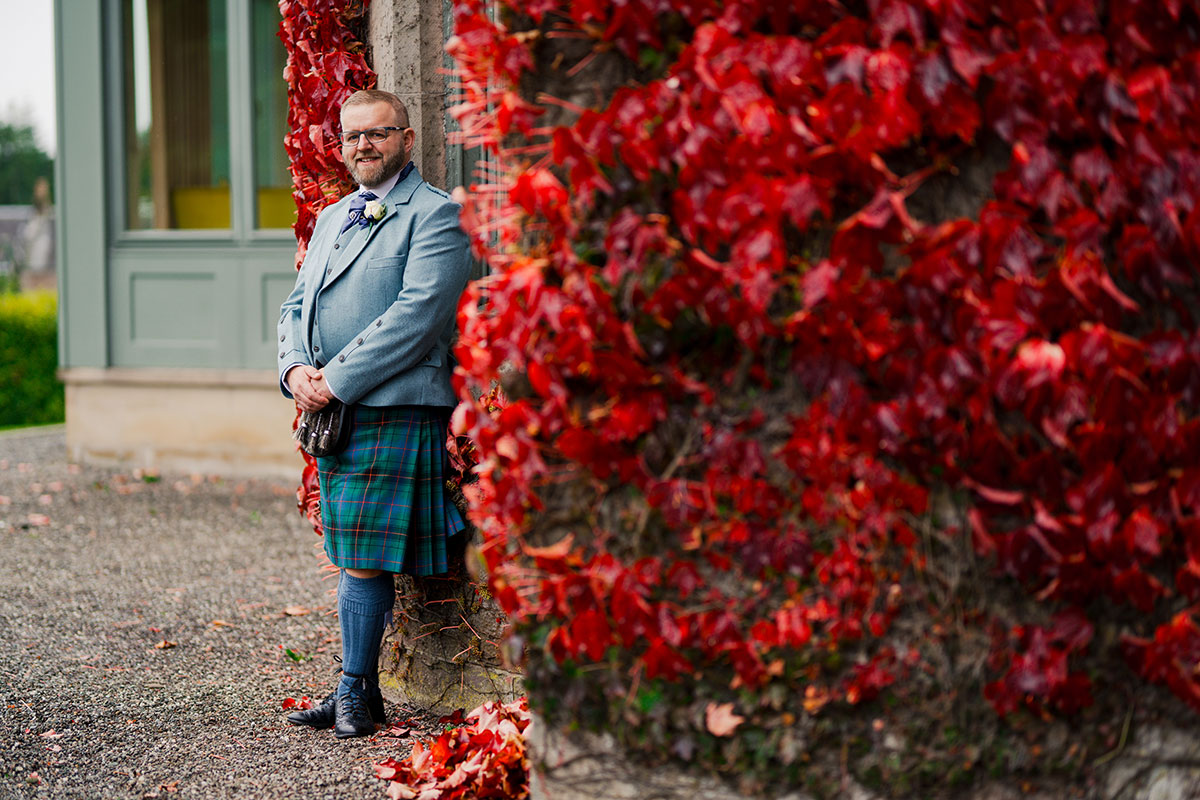 groom-in-kilt-standing-in-front-of-red-leaves-on-castle
