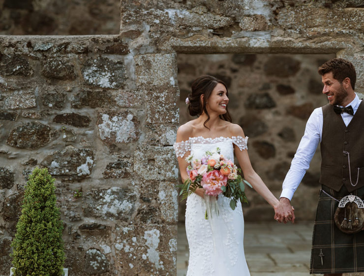 bride-and-groom-holding-hands-in-front-of-old-brick-wall