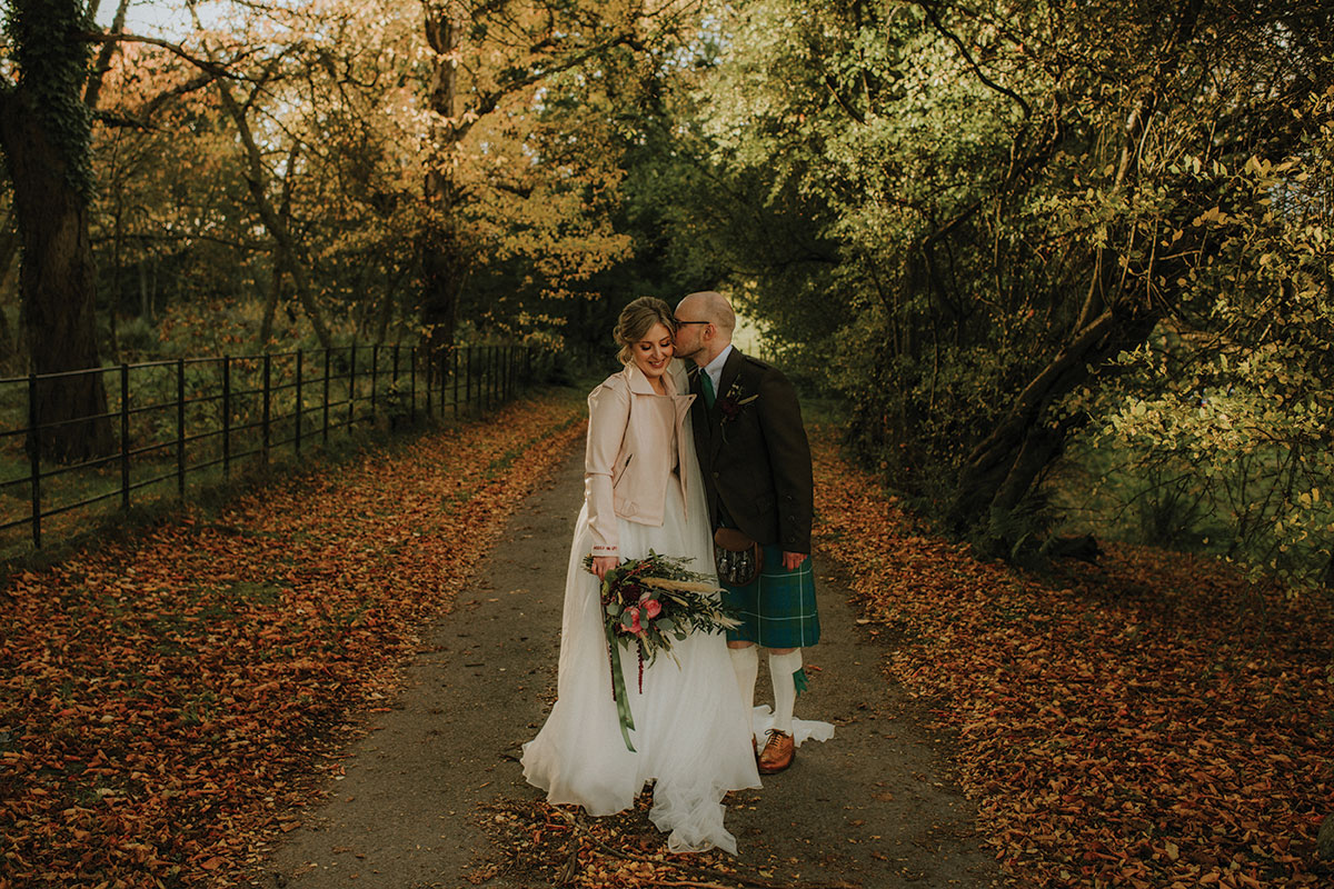 _bride-and-groom-walking-along-a-tree-line-path