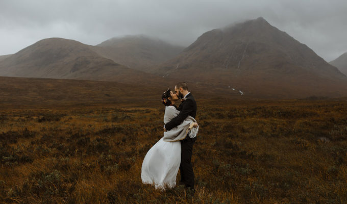 bride-and-groom-kissing-against-mountain-backdrop