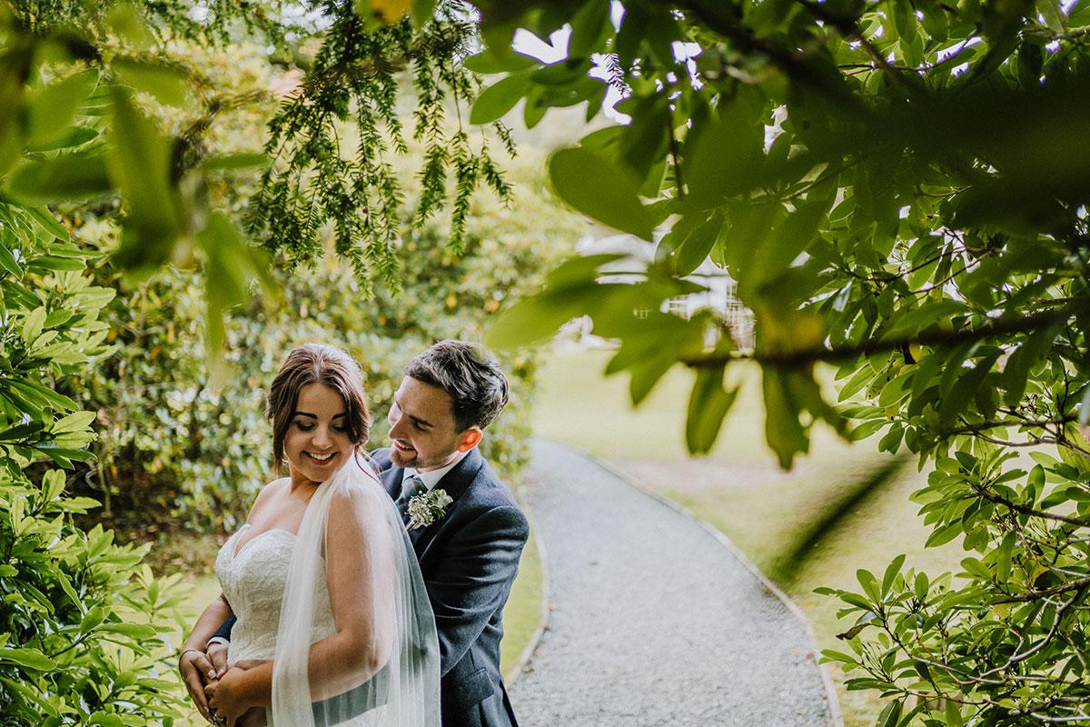 groom-embracing-bride-in-between-trees