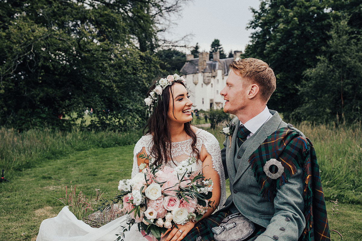bride-and-groom-sitting-in-front-of-tullibole-castle