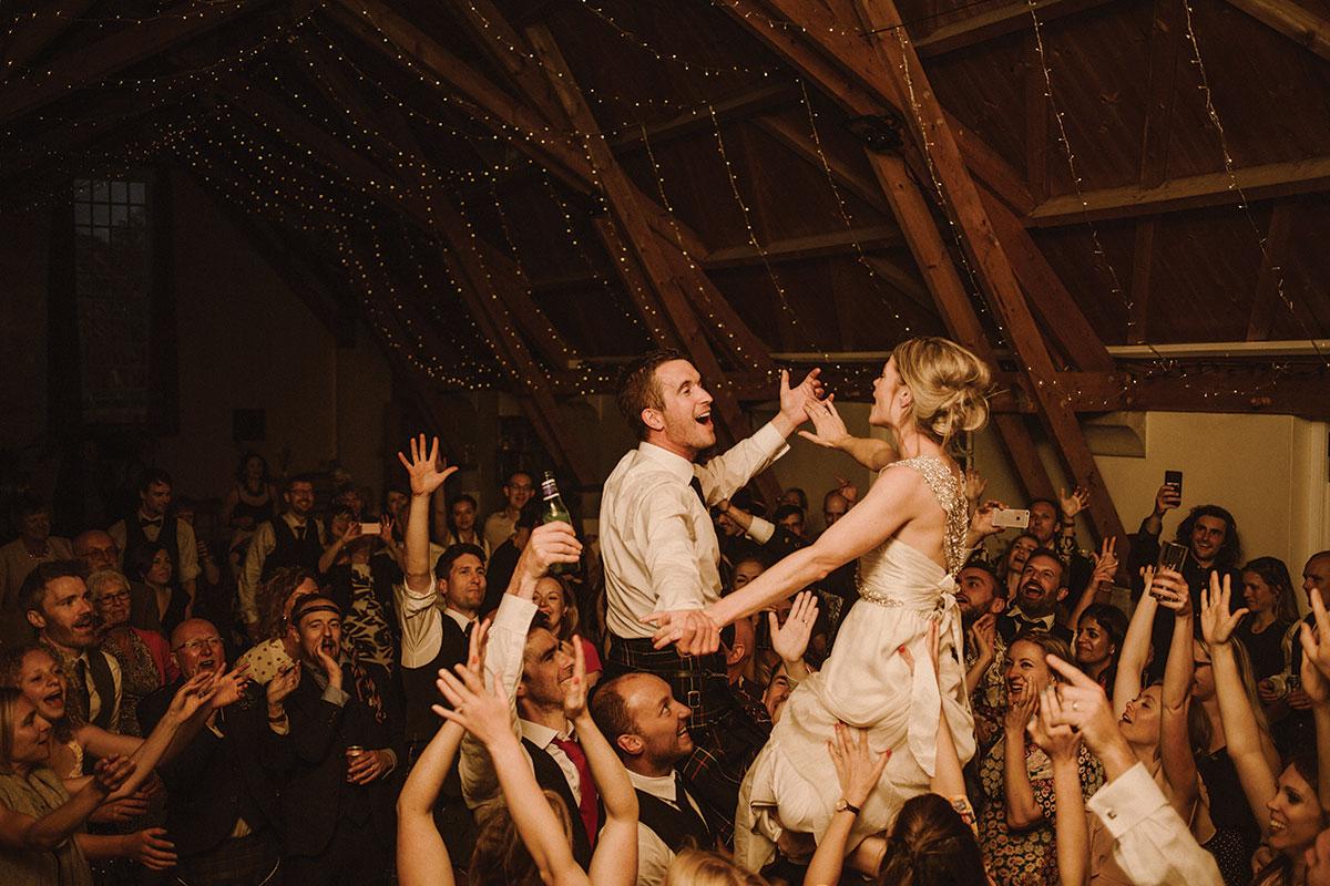 bride-and-groom-on-shoulders-dancing