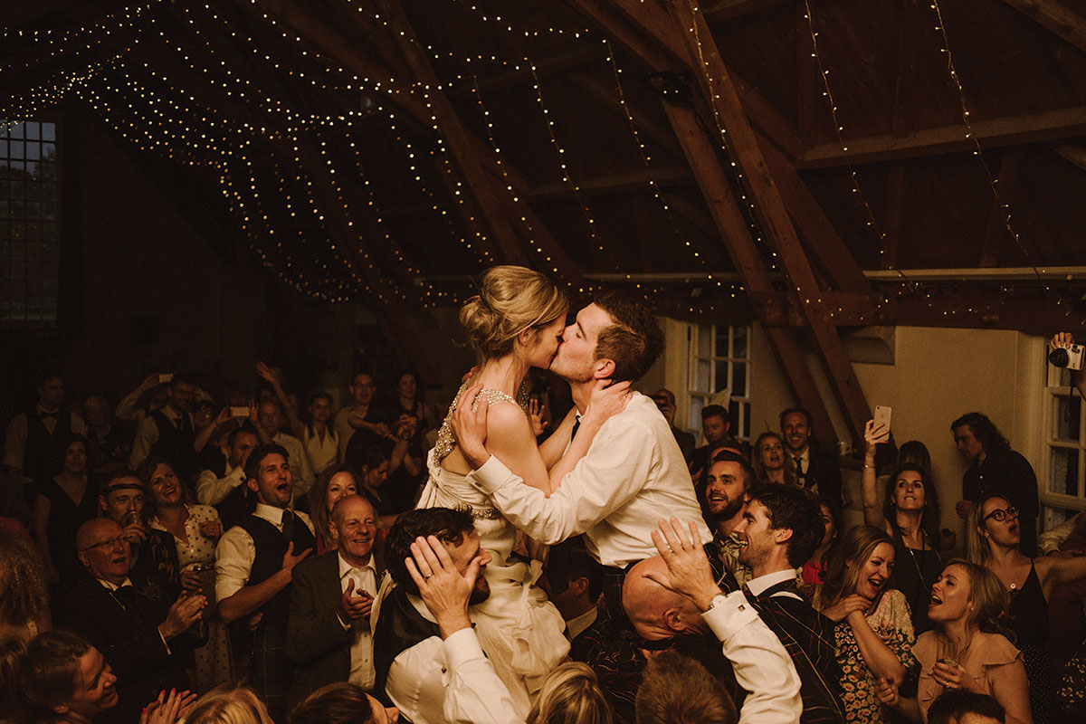 bride-and-groom-on-guests-shoulders-on-dancefloor