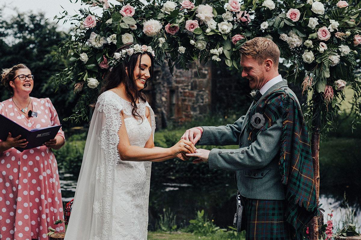 groom-putting-ring-onto-bride's-finger