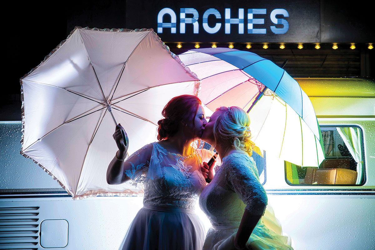 _brides-in-front-of-arches-sign-with-umbrellas