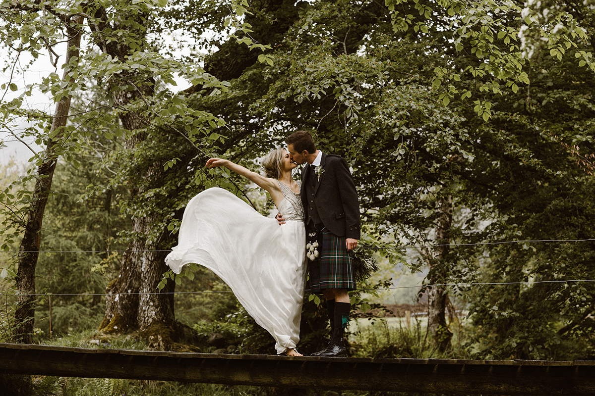 groom and bride on bridge flicking dress out