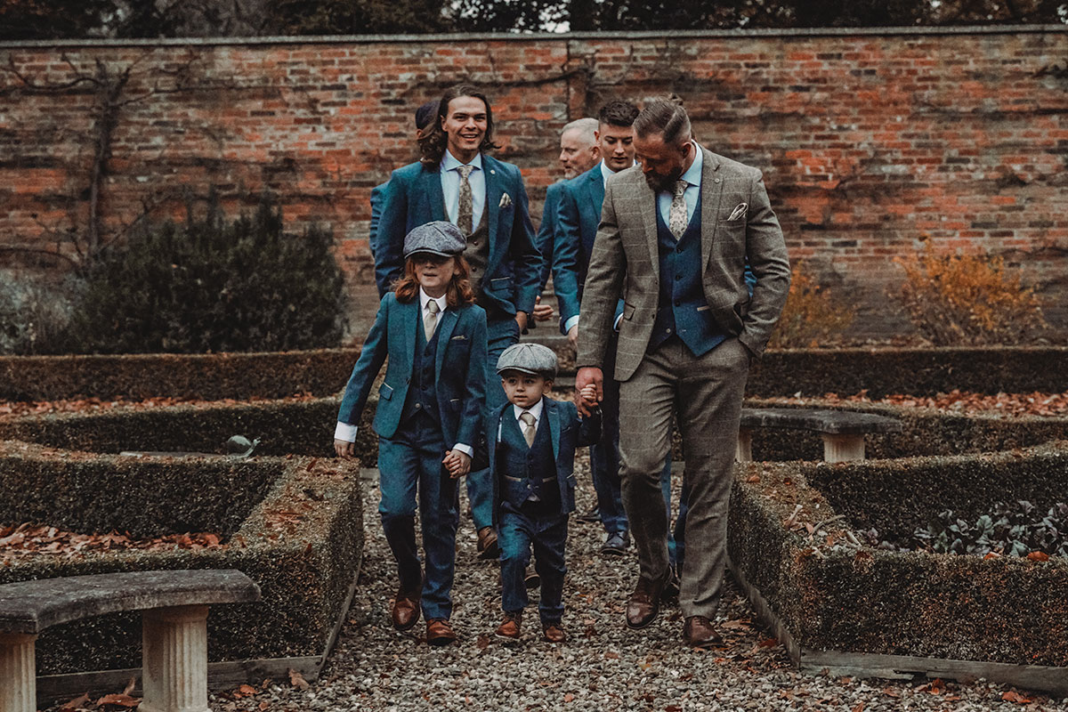 men and boys wearing suits in a garden