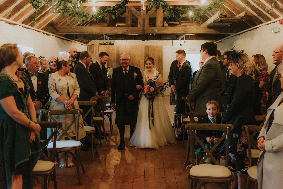 bride-walking-up-aisle-with-dad-in-venue-with-wooden-beam-ceiling