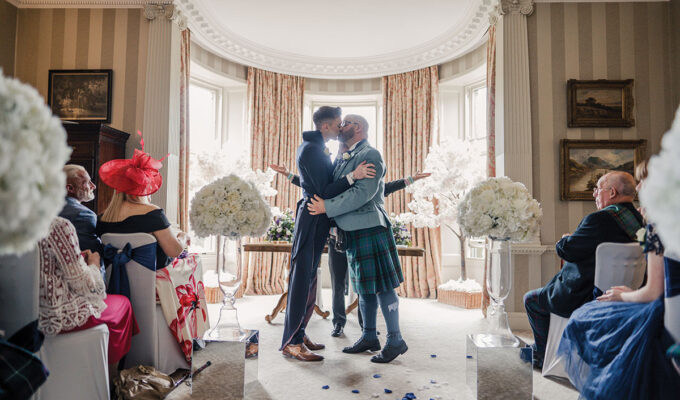 grooms-kissing-after-ceremony-with-white-flower-aisle-arrangements