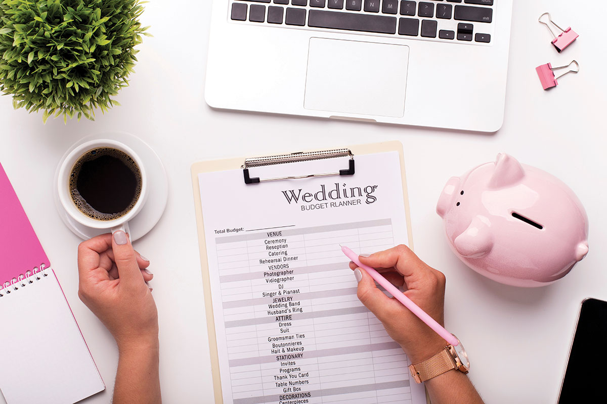 wedding budget planner and laptop on desk