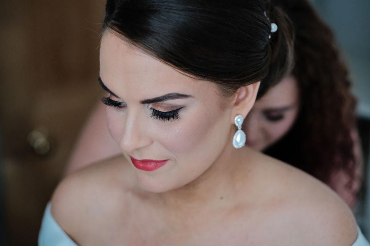 bride-getting-ready-bridesmaid-at-back-sorting-dress