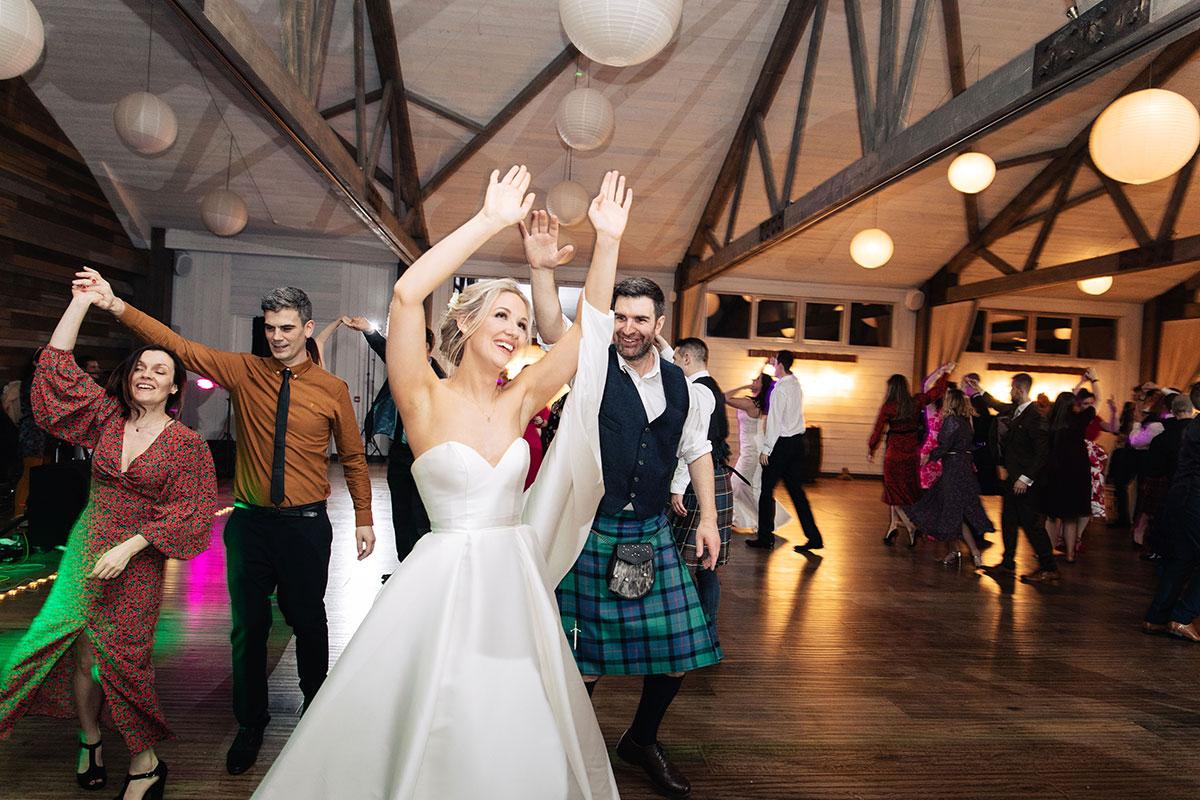 bride-groom-ceilidh-dancing-in-barn