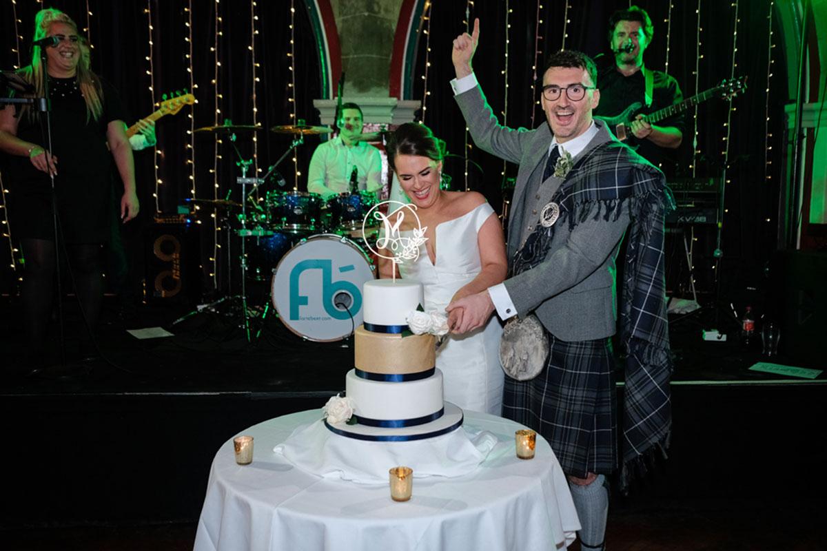 cutting-wedding-cake-at-oran-mor-with-wedding-band-in-backgorund