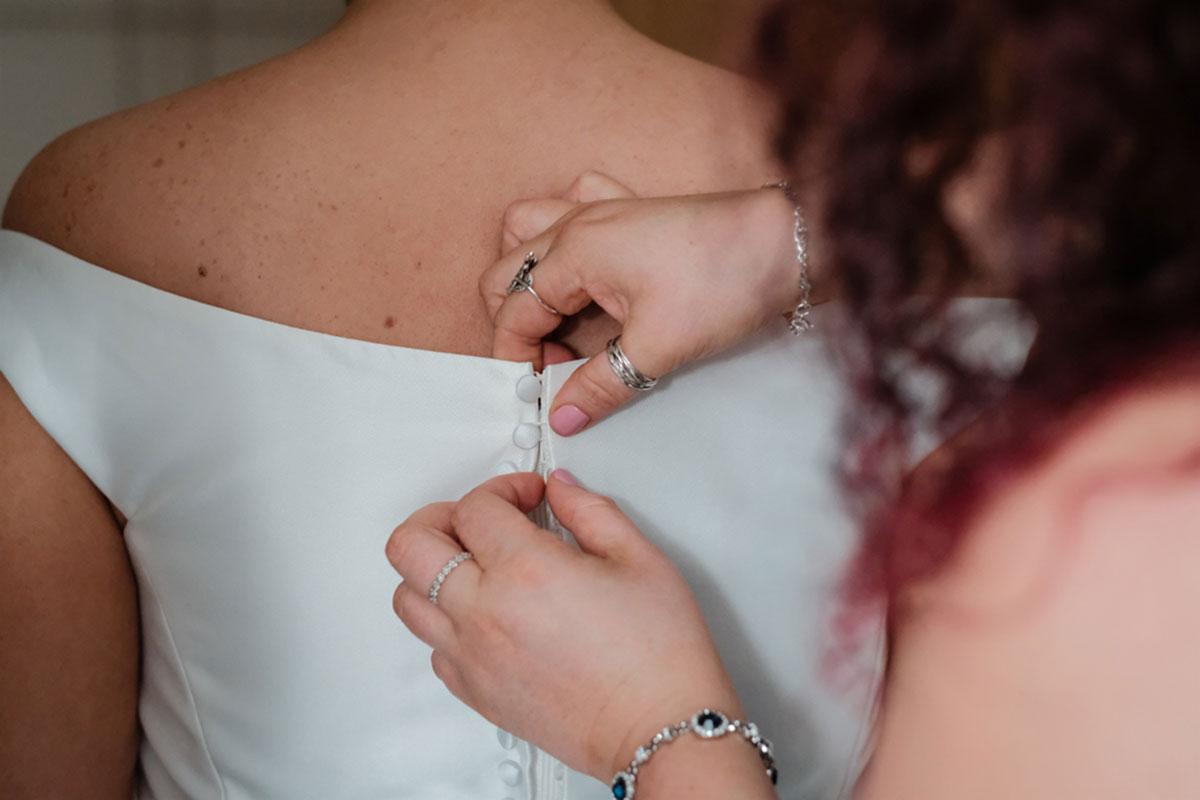 bridesmaid-fastening-buttons-on-wedding-dress
