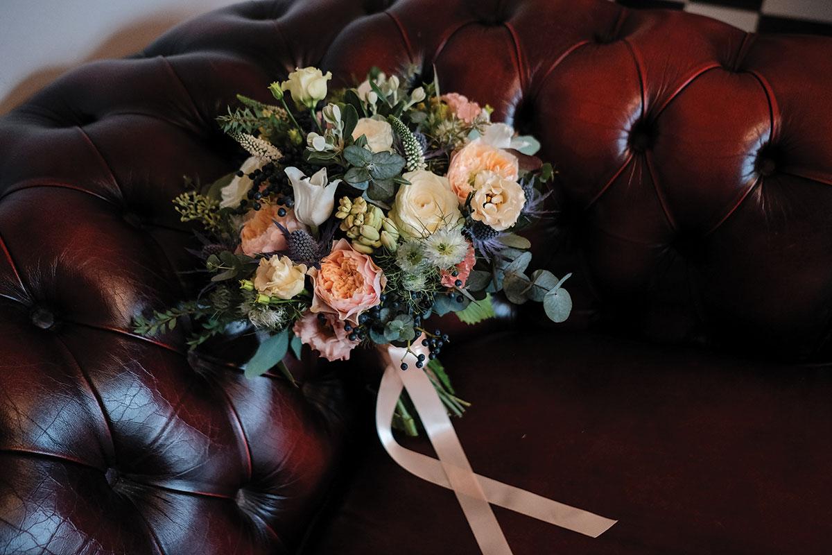 wedding-bouquet-on-oxblood-chesterfield-sofa